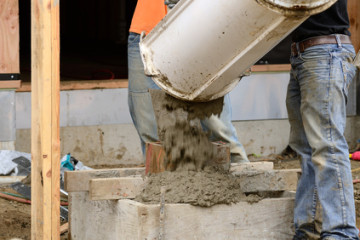 Worker working concrete on a post fondation support at a large commercial housing development in Oregon